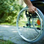 ss-close-up-of-male-hand-on-wheel-of-wheelchair-during-walk-in-park-155587316_630x460
